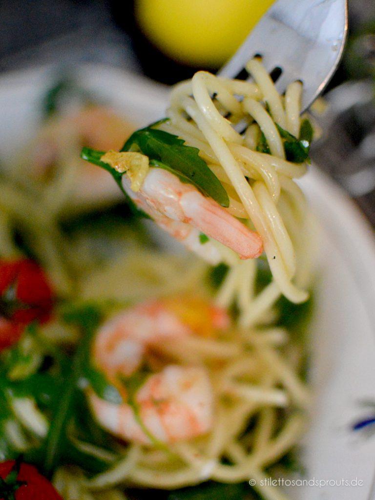 Eine Gabel mit aufgedrehten Spaghetti mit Rucola und Garnelen