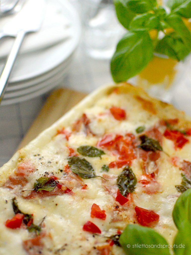 Basilikum, Schinken und Paprikawürfel werden im Ofen mit dem Mozzarella überbacken