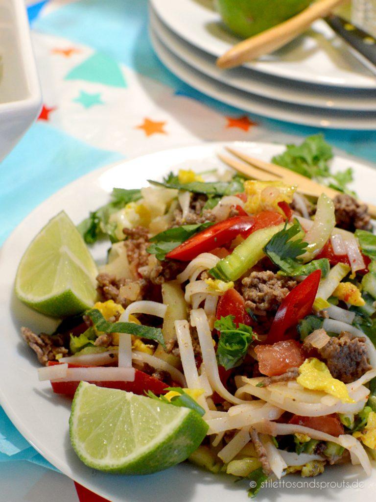 Ein Teller voll mit guten Dingen: Reisnudeln, knackiges Gemüse, Ei ,Hackfleisch und Limetten