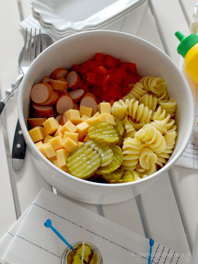 Salatzutaten sind Pasta, Paprika, Gürkchen, Würstchen und Käse