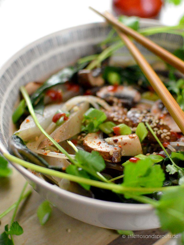 Als Topping dienen Koriander, scharfe Sauce und Sesam bei der asiatischen Nudelsuppe