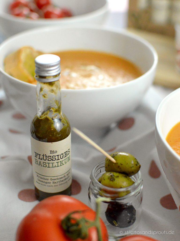 Flüssige Kräuter verfeinern die Tomaten Parmesan Suppe